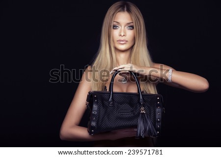 Portrait of beautiful blonde young woman posing with fashionable bag. - stock photo