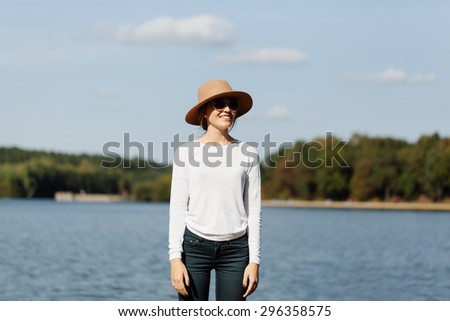 Portrait of beautiful blonde young woman standing near the lake, wearing sunglasses and hat. Nature background. - stock photo
