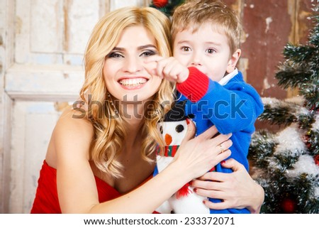 Portrait of beautiful blonde young woman with her little son over christmas background