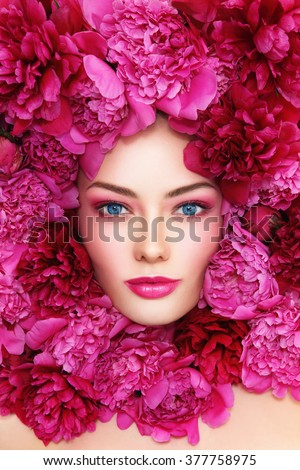 Portrait of beautiful blue-eyed woman with hot pink peonies around her face - stock photo