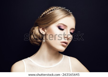 Portrait of beautiful bride at wedding dress in studio. Newlywed woman. Dark background. Lights makeup and braid hairstyle. Closed eyes. - stock photo