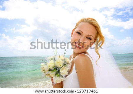 Portrait of beautiful bride standing by the beach - stock photo