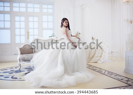Portrait of beautiful bride. Wedding dress with open back. Luxurious light interior - stock photo