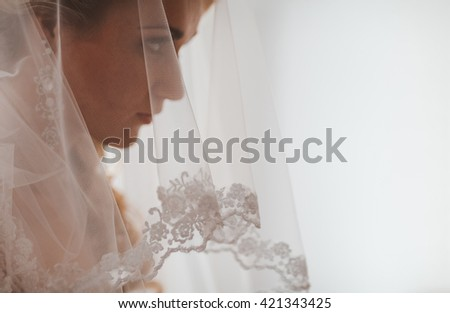 Portrait of beautiful bride with fashion veil posing at home at wedding morning. Makeup. Blondegirl with elegant hair styling. Wedding dress. Close Up - stock photo