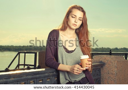 Portrait of beautiful brown haired girl standing and looking down. She keeping takeaway drink. Urban city scene. Outdoors portrait vintage film color imitation. Instagram-like toned image, colorized - stock photo