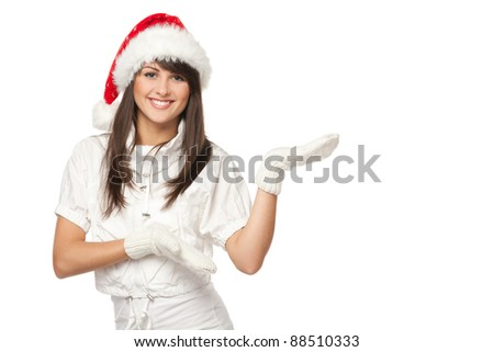 Portrait of beautiful brunette female in Santa hat pointing the side at blank copy space over white background - stock photo