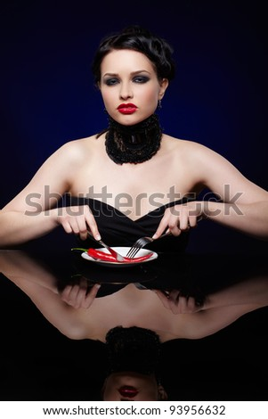 portrait of beautiful brunette girl cutting red hot spicy chilli pepper with fork and knife on white plate