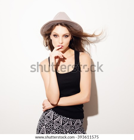 Portrait of beautiful brunette girl, fooling around in the studio on a white background - stock photo