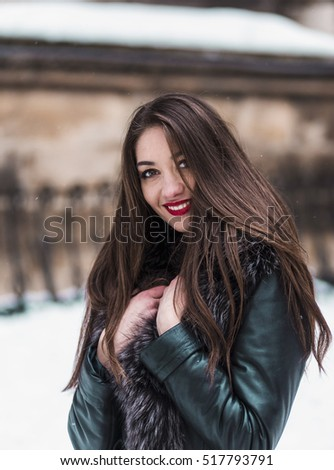 Portrait of beautiful brunette girl having fun in snowy winter time