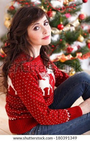 Portrait of beautiful brunette girl in a red sweater with a deer near the Christmas tree - stock photo