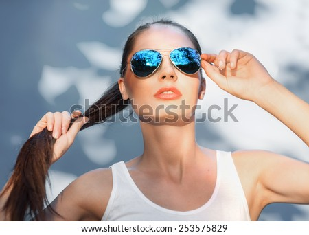 Portrait of beautiful brunette girl in mirrored blue sunglasses - stock photo