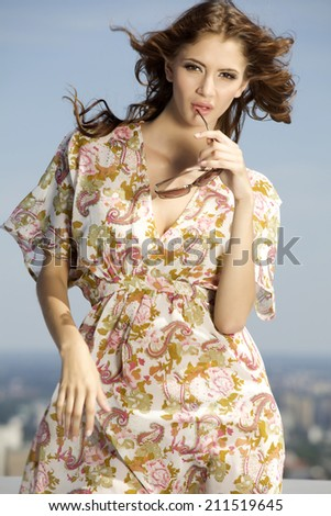 portrait of beautiful brunette girl in sunglasses on background blue sky - stock photo