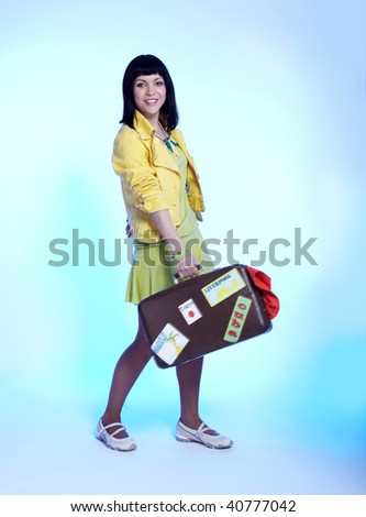 portrait of beautiful brunette girl posing on blue with luggage