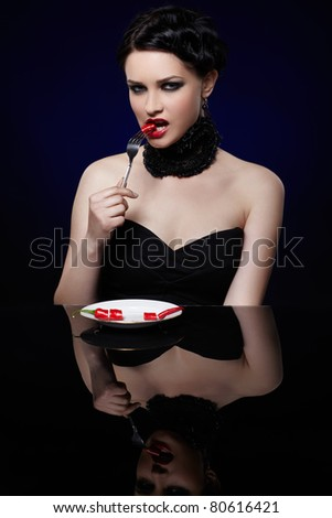 portrait of beautiful brunette girl posing with fork and single red hot spicy cayenne on white plate - stock photo