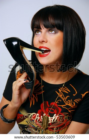 portrait of beautiful brunette girl posing with shoe