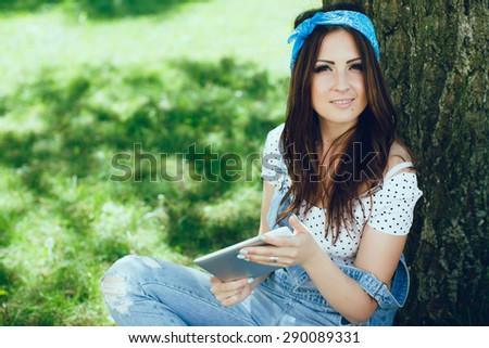 Portrait of beautiful brunette girl, sitting in the park, looking at camera. Wearing blue bandana, denim jumpsuit and top in speckled. Sunny day. Copy space. - stock photo
