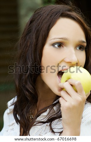 portrait of beautiful brunette girl with yellow apple