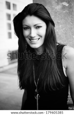 Portrait of beautiful brunette in a black shirt near the column, fashion photography, black and white photo