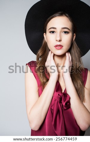 Portrait of beautiful brunette in black hat who held by the neck, posing in studio. - stock photo