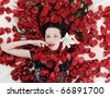 Portrait of beautiful brunette in rose petals - stock photo