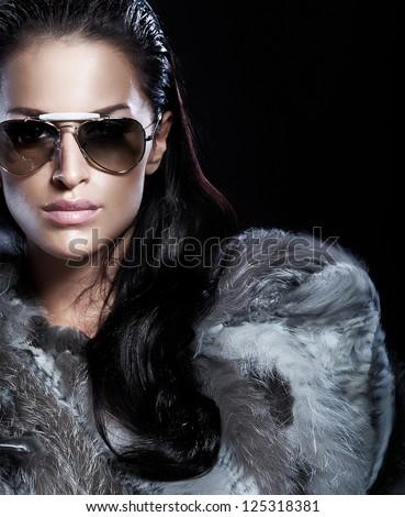 Portrait of beautiful brunette lady wearing fur and sunglasses. - stock photo
