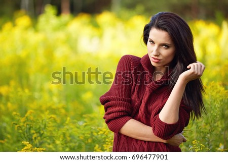 Portrait of beautiful brunette woman in autumn red sweater. Welcome warm autumn. Cute girl on a golden autumn background.