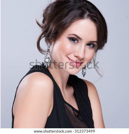 Portrait of beautiful brunette woman in black dress. Cosmetic Eyeshadows. Fashion photo - stock photo