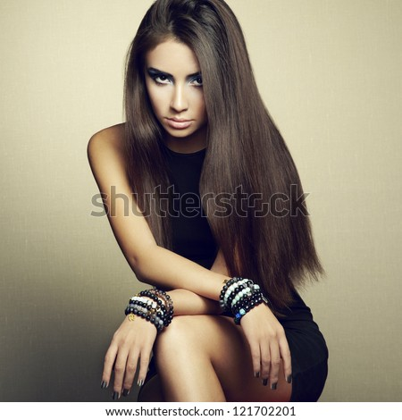 Portrait of beautiful brunette woman in black dress. Fashion photo - stock photo