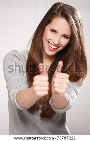 Portrait of beautiful brunette woman isolated on natural background, showing thumbs up - stock photo