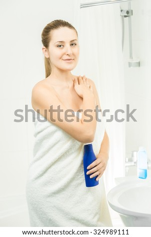 Portrait of beautiful brunette woman using lotion at shower - stock photo