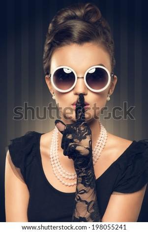 portrait of beautiful brunette woman wearing pearl  jewelry and sunglasses. retro style - stock photo