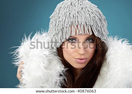 Portrait of beautiful brunette woman wearing sexy winter clothes on blue background