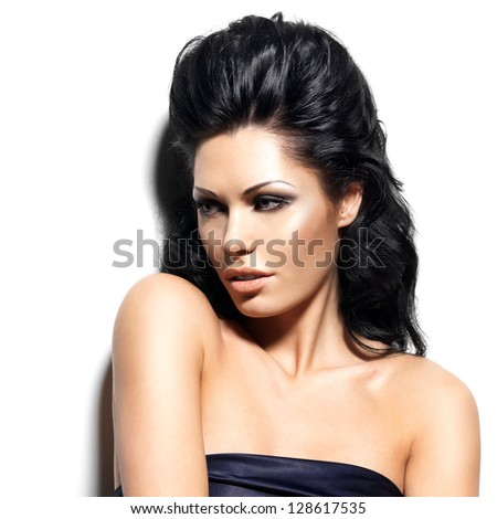 Portrait of beautiful brunette woman with creative hairstyle. Closeup face of fashion model posing at studio about the wall. - stock photo
