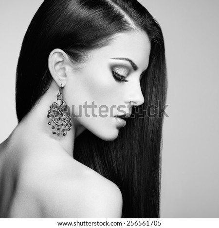 Portrait of beautiful brunette woman with earring. Perfect makeup. Fashion photo. Black and White