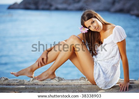 Portrait of beautiful brunette woman with long legs posing over sea view - stock photo