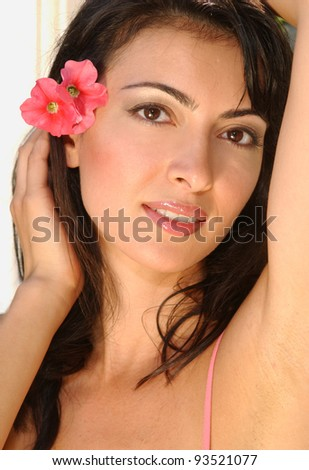 Portrait of beautiful Brunette woman with red flower in the hair - stock photo