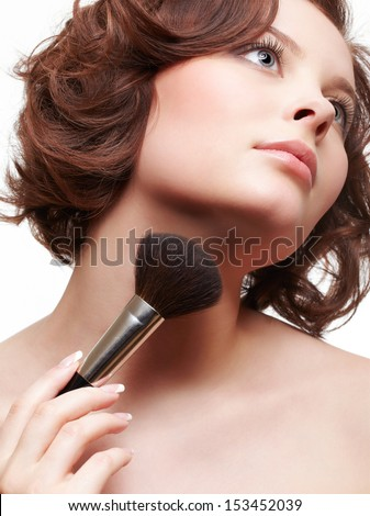 portrait of beautiful brunette young woman applying powder with make-up brush