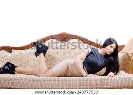 Portrait of beautiful brunette young woman having fun lying on the bed in black sneakers and leather skirt looking at the camera - stock photo