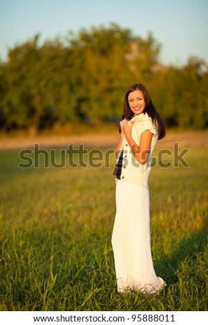 portrait of beautiful brunette young woman in countryside