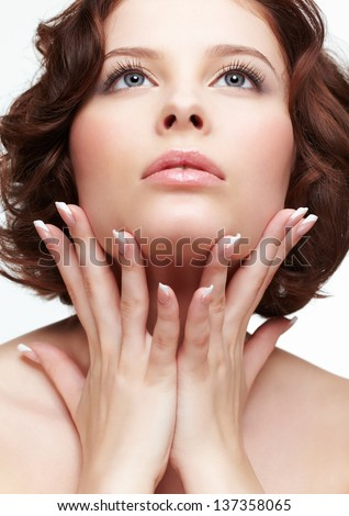portrait of beautiful brunette young woman with french manicure touching her face - stock photo
