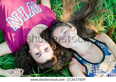 portrait of 2 beautiful brunette young women best friends having fun relaxing & happy smiling looking at camera while lying on green grass outdoors copy space background - stock photo