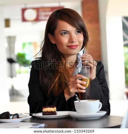 Portrait of beautiful business woman drinking water at cafe