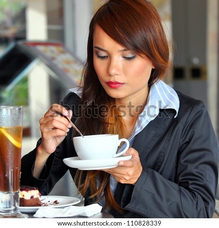 Portrait of beautiful business woman drinking water at cafe - stock photo
