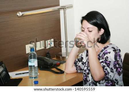 Portrait of beautiful business woman drinking water at office - stock photo