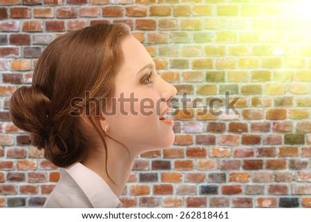 Portrait of beautiful business woman in profile, against background of brick wall - stock photo