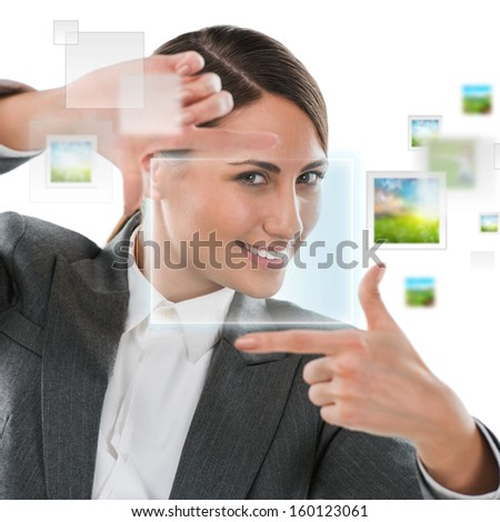 Portrait of beautiful business woman making frame gesture on white background and virtual pictures surrounding her - stock photo