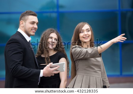 Portrait of beautiful business woman meeting with clients or partners outdoors. Successful attractive caucasian real-estate agent showing property to happy laughing young couple - stock photo