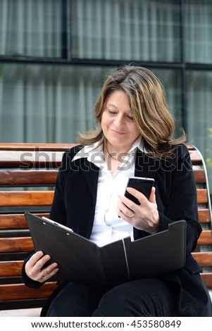 Portrait of beautiful business woman reading clipboard and holding her phone. Outdoors. - stock photo