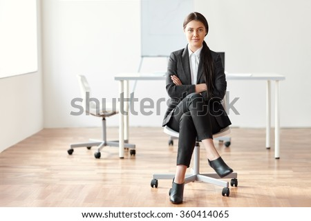 Portrait of beautiful business woman sitting on chair in the office - stock photo