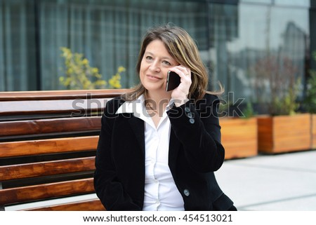 Portrait of beautiful business woman talking at her phone while sitting on a bench. Outdoors. - stock photo